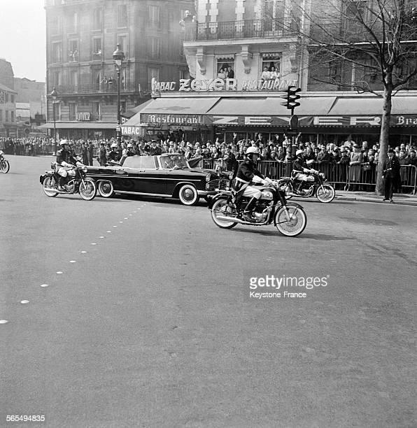 Foule venue voir passer la voiture décapotable du président du conseil soviétique Nikita Khrouchtchev encadrée par les gendarmes motards à Paris...