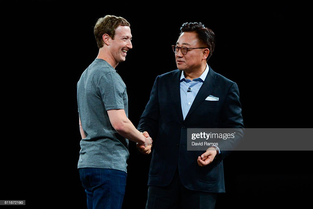 Founder and CEO of Facebook Mark Zuckerber and President of Mobile Communications Business of Samsung DJ Koh shake hands during the presentation of...