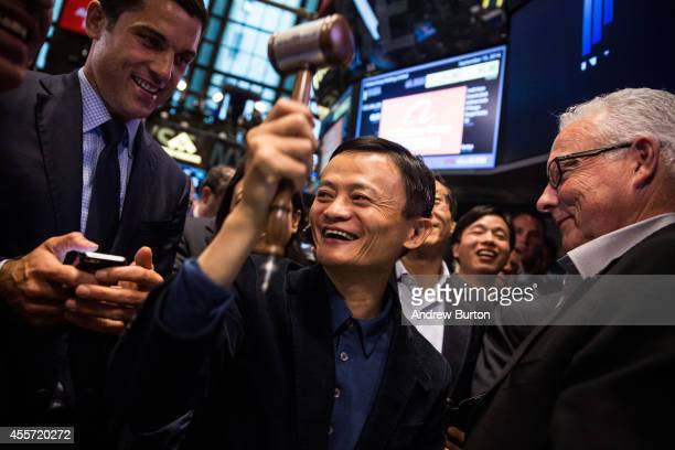 Founder and Executive Chairman of Alibaba Group Jack Ma celebrates as the Alibaba stock goes live during the company's initial price offering at the...