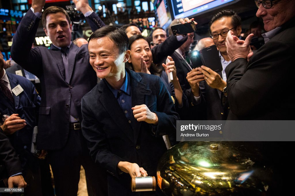 Founder and Executive Chairman of Alibaba Group Jack Ma rings a bell to celebrate as the Alibaba stock goes live during the company's initial price...