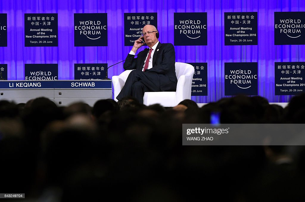 Founder and executive chairman of the World Economic Forum, Klaus Schwab, listens as Chinese Premier Li Keqiang (not pictured) gives a speech on the first day of the World Economic Forum in Tianjin on June 27, 2016. The annual World Economic Forum New Champions meeting brings together business, economic and political leaders. / AFP / POOL / WANG