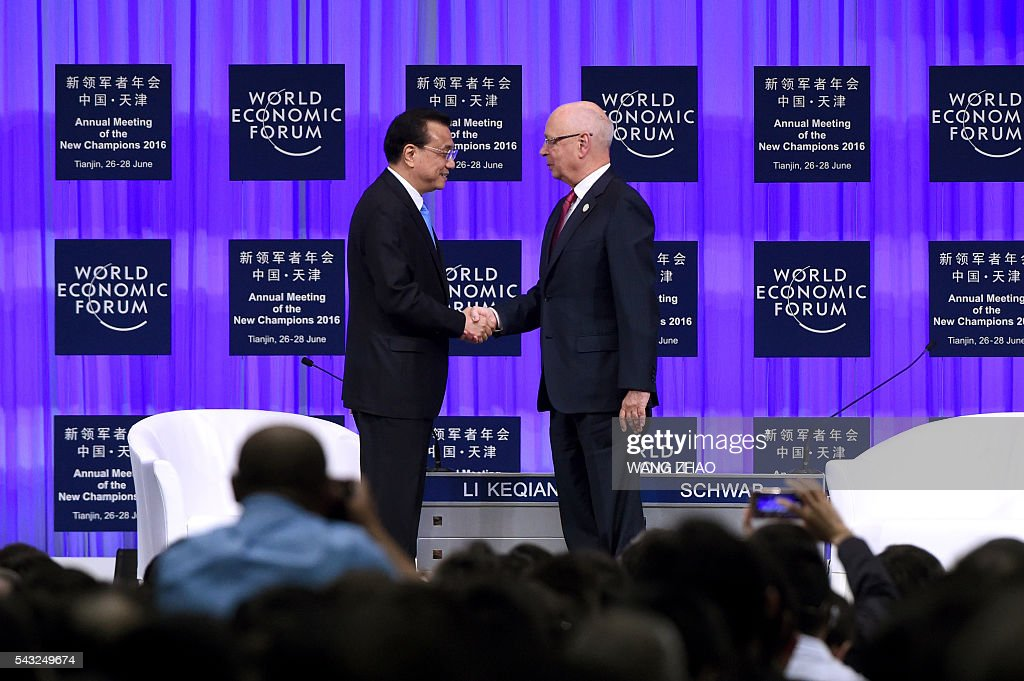 Founder and executive chairman of the World Economic Forum, Klaus Schwab (R), shakes hands with Chinese Premier Li Keqiang on the first day of the World Economic Forum in Tianjin on June 27, 2016. The annual World Economic Forum New Champions meeting brings together business, economic and political leaders. / AFP / POOL / WANG