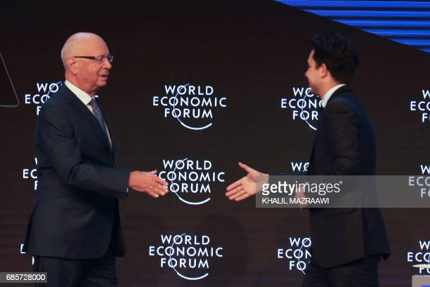 Founder and Executive Chairperson of the World Economic Forum Klaus Schwab prepares to shake hands with Jordan's Crown Prince Hussein the son of King...