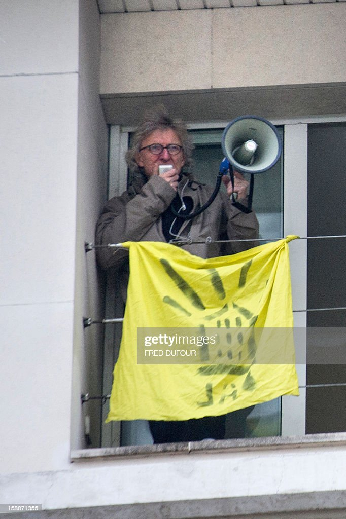 Founder and spokesperson for the 'Right to Housing Association' ('Droit Au Logement', DAL) Jean-Baptiste Eyraud speaks using a megaphone as he takes part in an operation to requisition a building with French 'Jeudi Noir' ('Black Thursday') collective's members on January 2, 2013 in Paris.