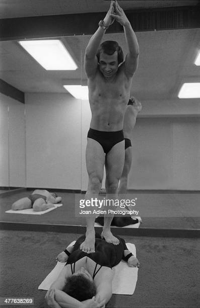 Founder and teacher of Bikram Yoga Bikram Choudhury assisting a client at his yoga studio in Beverly Hills California