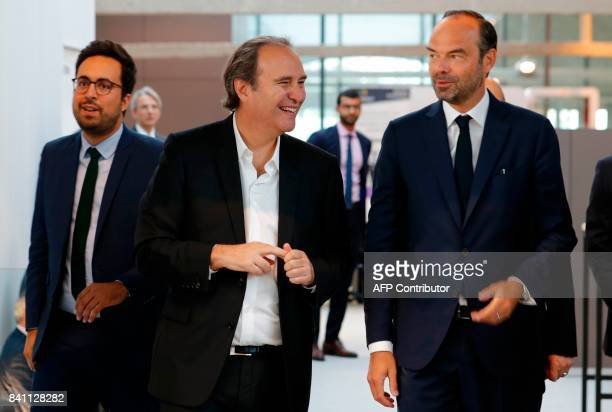 Founder of French broadband Internet provider Iliad Xavier Niel speaks with French Prime Minister Edouard Philippe next to Minister for the Digital...
