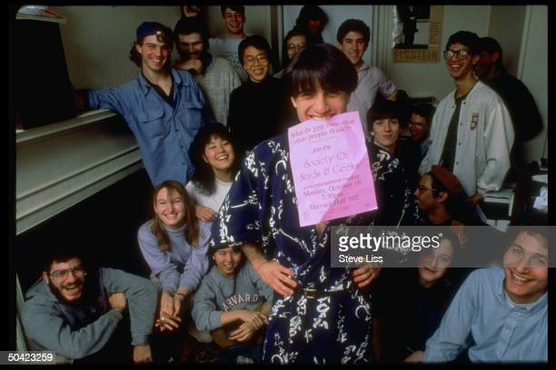 Founder of Harvard Univ campus group SONG Jeremy Kahn holding flyer for his org w other nerds and geeks in bkgrd
