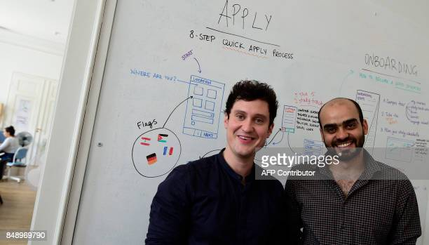 Founder of Kiron Markus Kressler and Kiron student Moataz Ghannam pose at the Berlin office before an AFP interview in Berlin on September 6 2017...