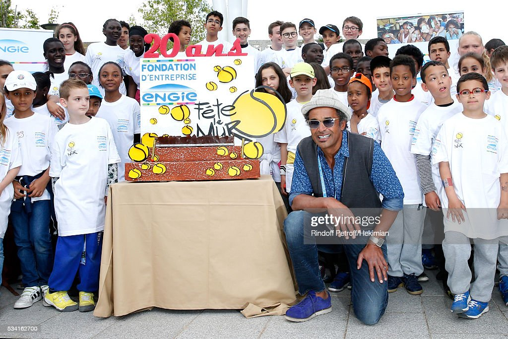 Founding President of 'Fete le Mur' Association, <a gi-track='captionPersonalityLinkClicked' href=/galleries/search?phrase=Yannick+Noah&family=editorial&specificpeople=215249 ng-click='$event.stopPropagation()'>Yannick Noah</a>, blows out candles for the 20th Anniversary of the Association, with children of the Association and the Engie Foundation in front of the Tree Wind Turbine during the 2016 French Tennis Open - Day Four at Roland Garros on May 25, 2016 in Paris, France.