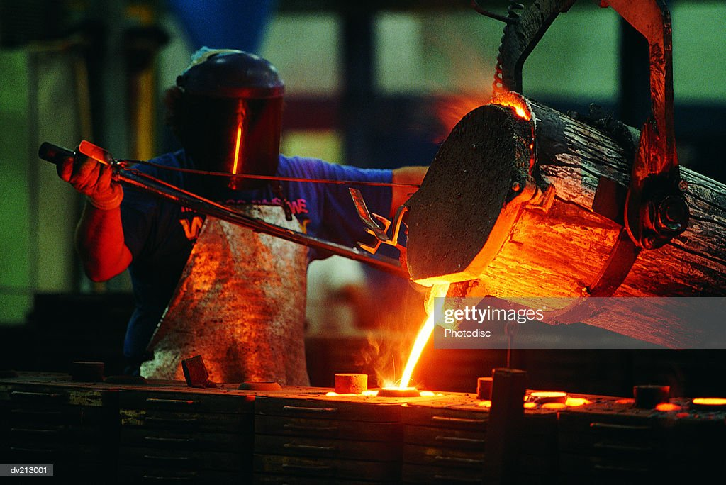 Foundry worker pouring steel