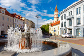 Fountain and church in the old city summer sunny day, Vilnius, Lithuania, Baltic states.
