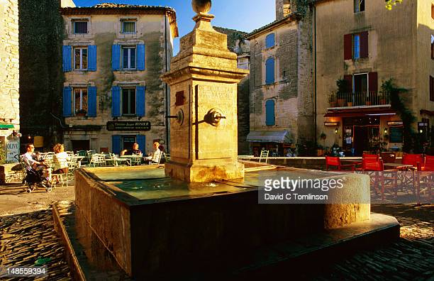 Fountain and outdoor cafes in village square, Gordes.