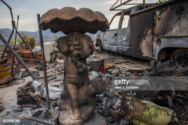 A fountain and truck parked in front of a home and property lies in ruin as it was one of three homes and a shed were destroyed in the the La Tuna...