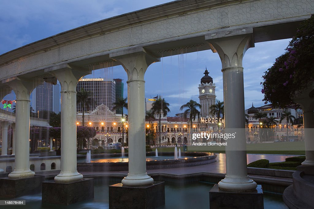 Fountain at Merdeka Square with Sultan Abdul Samad Building showing between pillars at dusk.