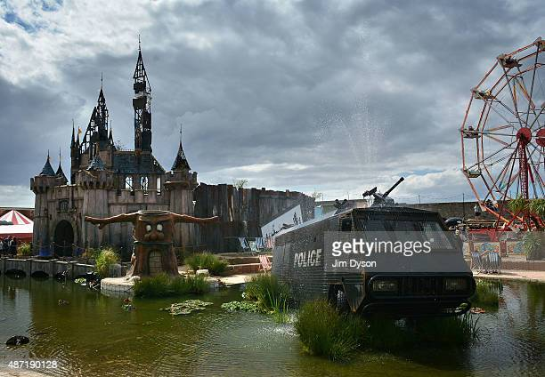 A fountain by Banksy made from an abandoned police riot vehicle is displayed in front of the fairy castle as Banksy's Dismaland Bemusement Park opens...