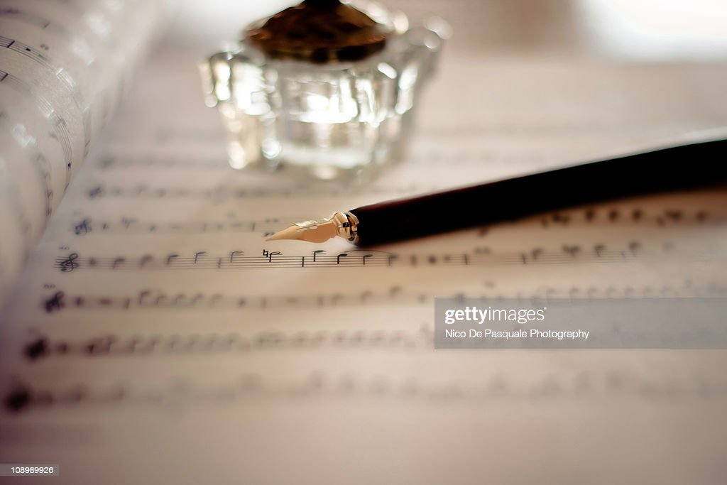 Fountain pen atop sheet music : Stock Photo