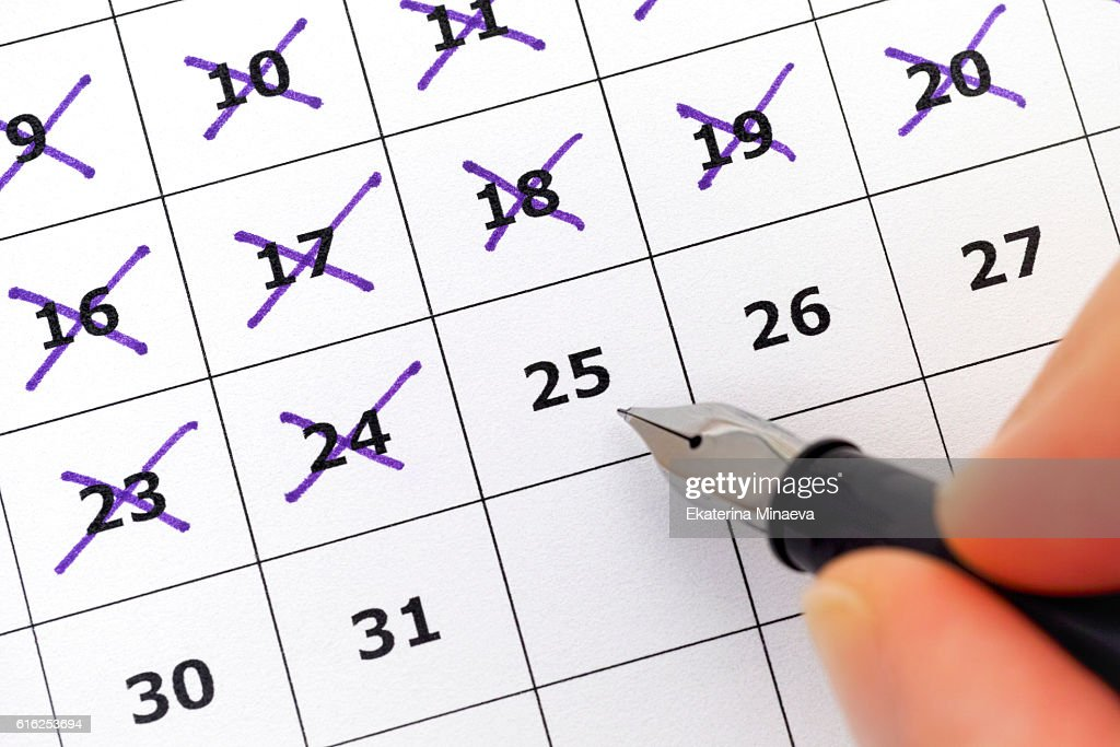 Fountain pen in person hand marking days on calendar : Stock Photo