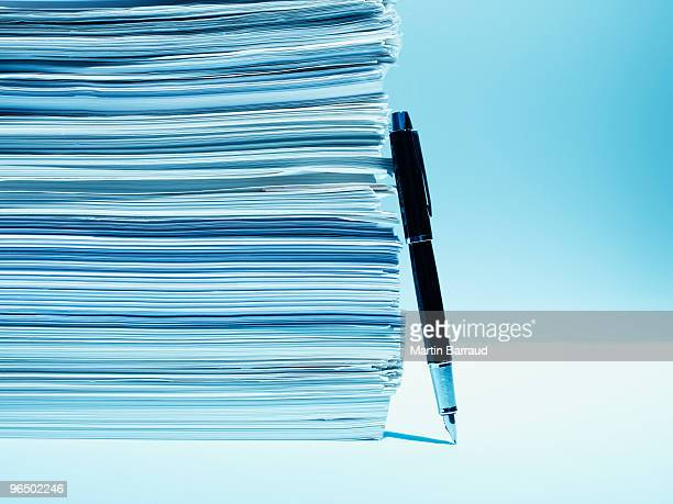 Fountain pen leaning against stack of paper