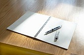 Fountain pen with top removed, placed on blank pages of white notepad lying on wooden desk