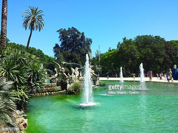 Fountains In Pond At Park Against Clear Blue Sky