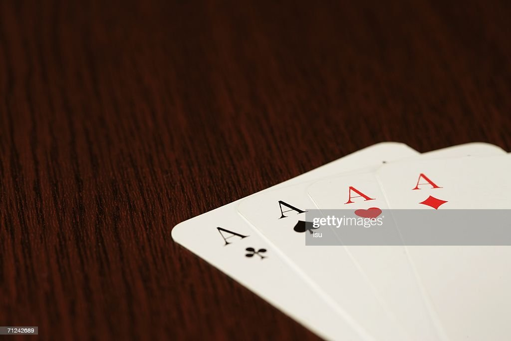 Four aces on a wooden underlay, close-up : Stock Photo