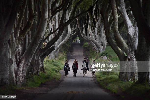 Four actors on horseback dressed in Game of Thrones related costumes carry the Queen's Baton as they make their way way along the Dark Hedges on...
