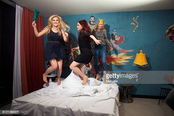 Four adult friends dancing on hotel bed