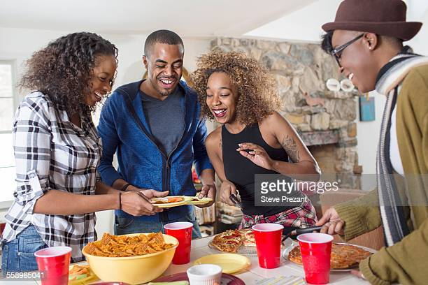 Four adult friends eating party food in kitchen