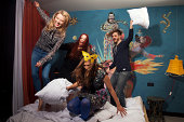 Four adult friends having pillow fight on hotel bed