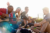 Four adult friends partying on Bournemouth beach, Dorset, UK