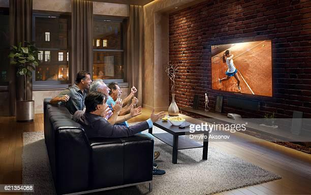 Four adult men watching Tennis game on TV