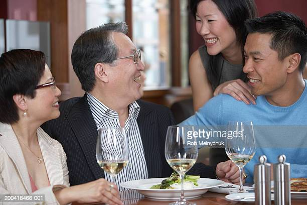 Four adults dining and talking in restaurant
