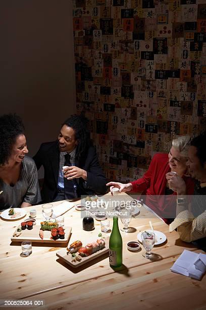 Four adults drinking sake at table in sushi bar, laughing