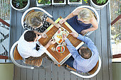 Four adults eating appetizers at outdoor table, overhead view