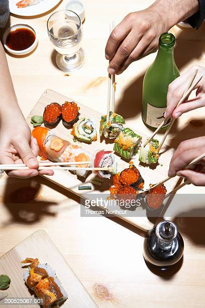 Four adults eating sushi, mid section, elevated view