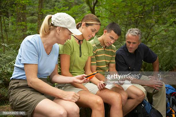 Four adults looking at topographical map and using GPS