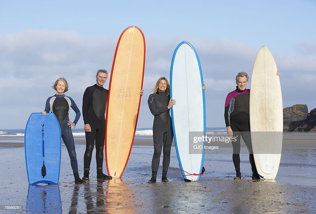 Four adults on the beach with surfboards and a boogie board : Stock Photo