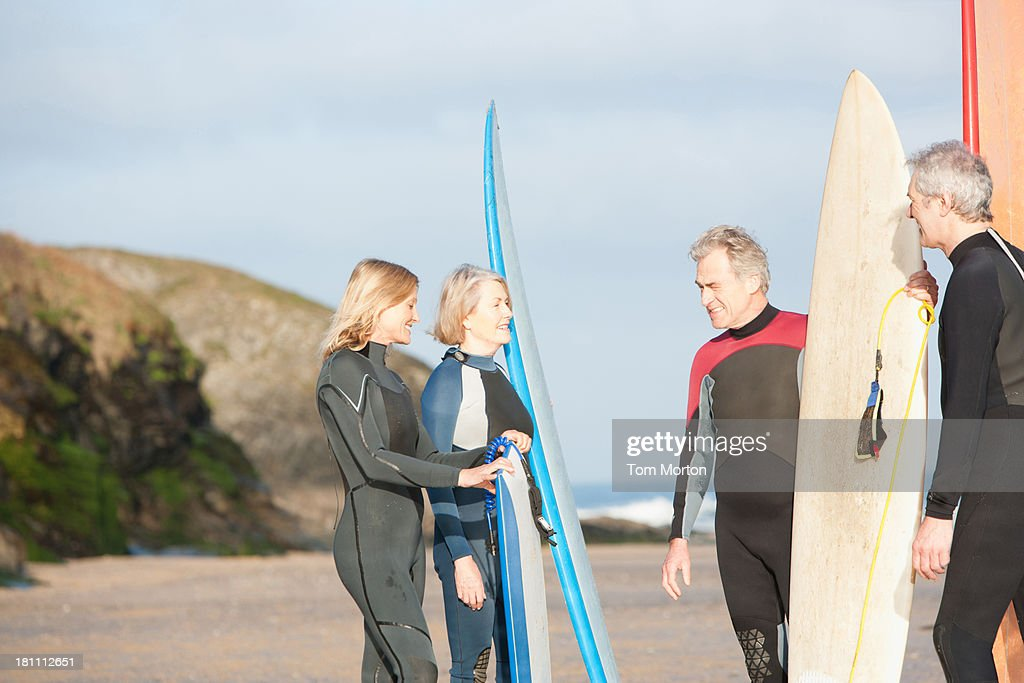 Four adults on the beach with surfboards : Stock Photo