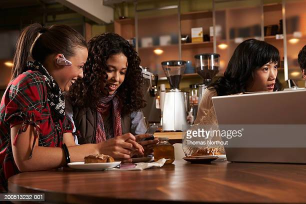Four adults sitting at table in cafe, talking and laughing
