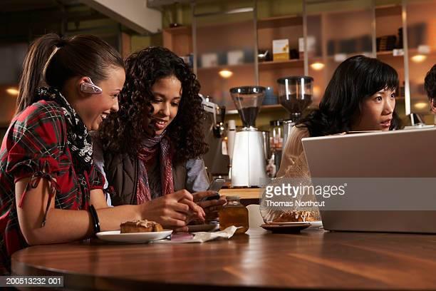Vier Erwachsenen sitzt am Tisch im Café, zu reden und Lachen