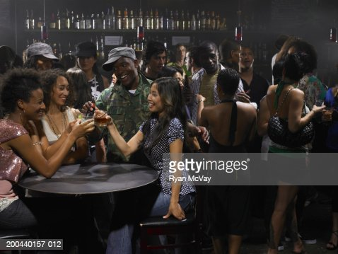 Four adults toasting with beer and cocktails in nightclub, smiling : Stock Photo