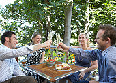 Four adults toasting with champagne at outdoor table, laughing