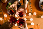 Four adults toasting with red wine, overhead view, close-up of hands