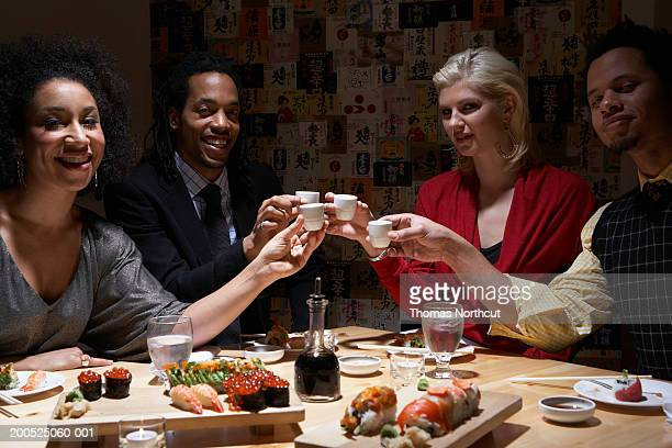 Four adults toasting with sake in sushi bar, smiling, portrait