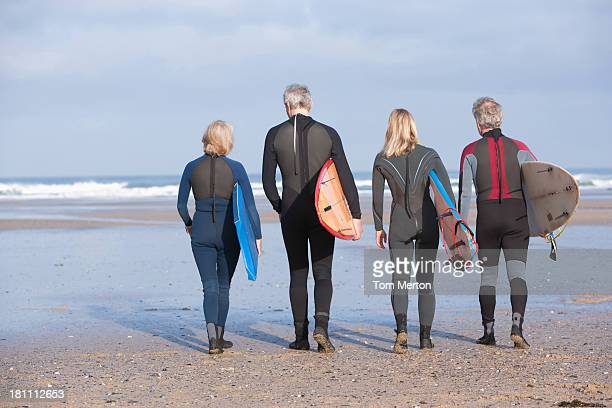 Four adults walking on the beach with surfboards