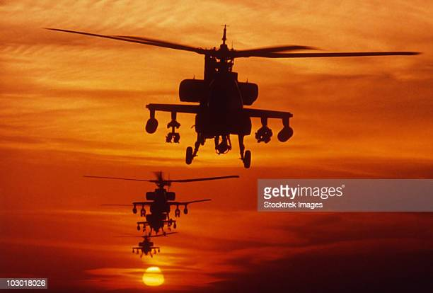 Four AH-64 Apache anti-armor helicopters fly in formation at dusk.