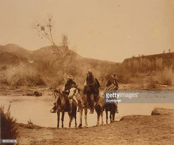Four Apache men on horseback at the edge of a stream