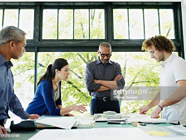 Four architects examining plans at table in office
