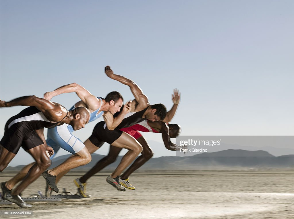 Four athletes from starting block, side view (blurred motion) : Stock Photo
