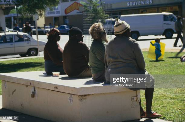 Four Australian Aborigines sitting by the roadside in Alice Springs Australia 1986